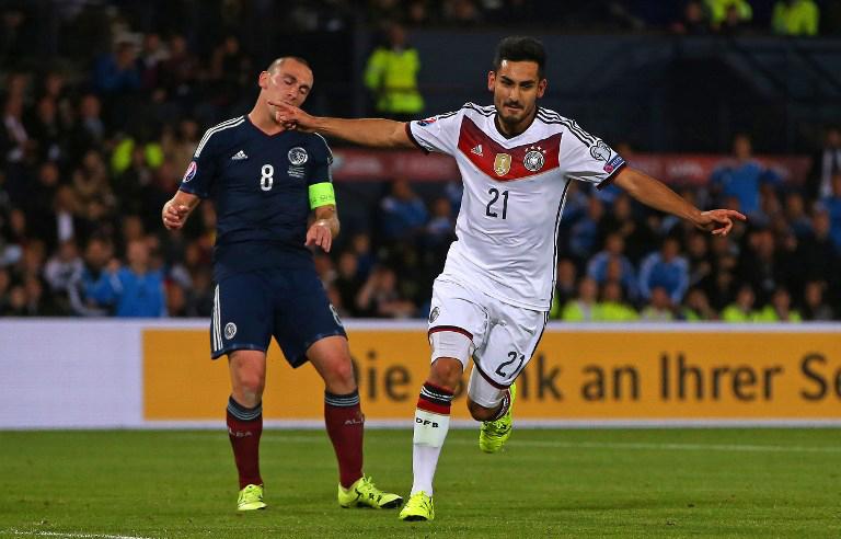 Ilkay Gundogan (R) feiert sein Tor gegen Schottland - der Schotte Scott Brown kann nur zuschauen. AFP PHOTO / IAN MACNICOL
