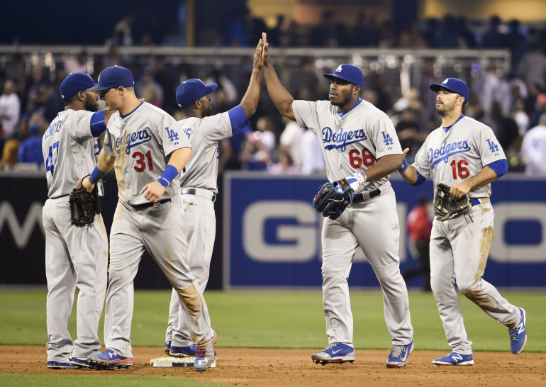 SAN DIEGO, CA - JUNE 12: Los Angeles Dodgers players high-five after beating the San Diego Padres 4-3 in a baseball game at Petco Park June 12, 2015 in San Diego, California. (Photo by Denis Poroy/Getty Images)